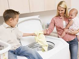 Mother shows son how to laundry
